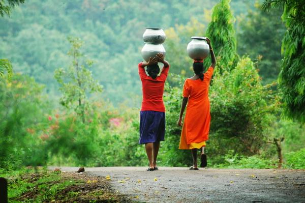 Tribal girls drinking water - Ranjan Panda